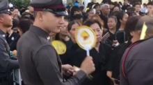 ตำรวจคอยพัดคลายร้อนให้ประชาชนที่ต่อแถวรอคอยเข้าจุดคัดกรอง